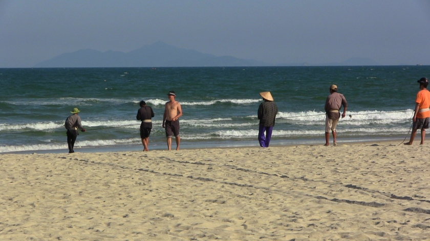 Vietnamese fishermen in Da Nang on November 30, 2013, pulling ashore their nets as a shirtless swimmer walks past them. (Credit: Nissa Rhee).