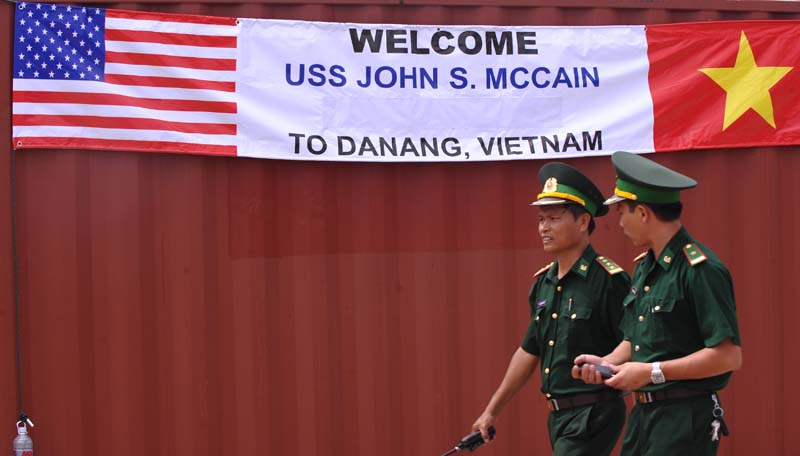 Two Vietnamese border-guard officers walk past a banner welcoming the port call by the US destoryer USS John S. McCain at Tien Sa port in the central costal city of Danang on August 10, 2010. (HOANG DINH NAM/AFP/Getty Images)
