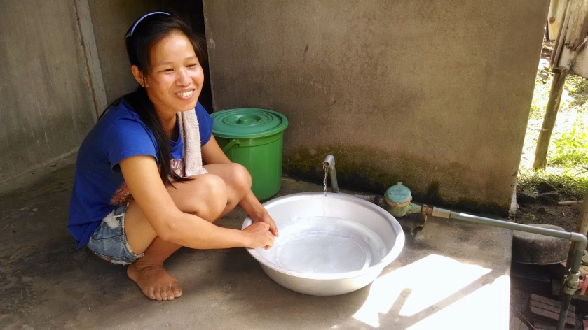 A woman living in Nghia Tho village in Quang Ngai Provence shows me the water that now flows into her house thanks to the well. (Photo by Nissa Rhee, June 2014)