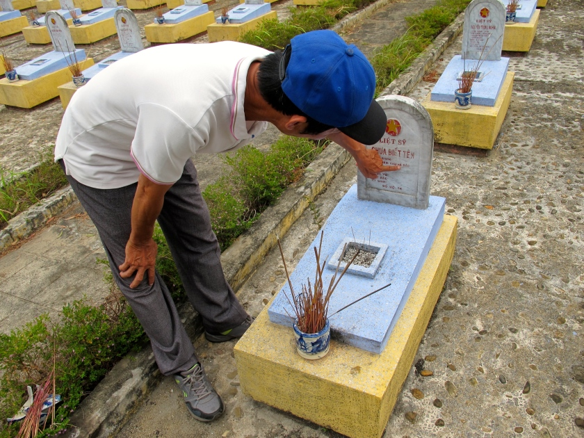 Tran Hoa, my guide, shows me one of the hundreds of graves for unknown soldiers at the Route 9 Cemetery. (Photo by Nissa Rhee, June 2014)