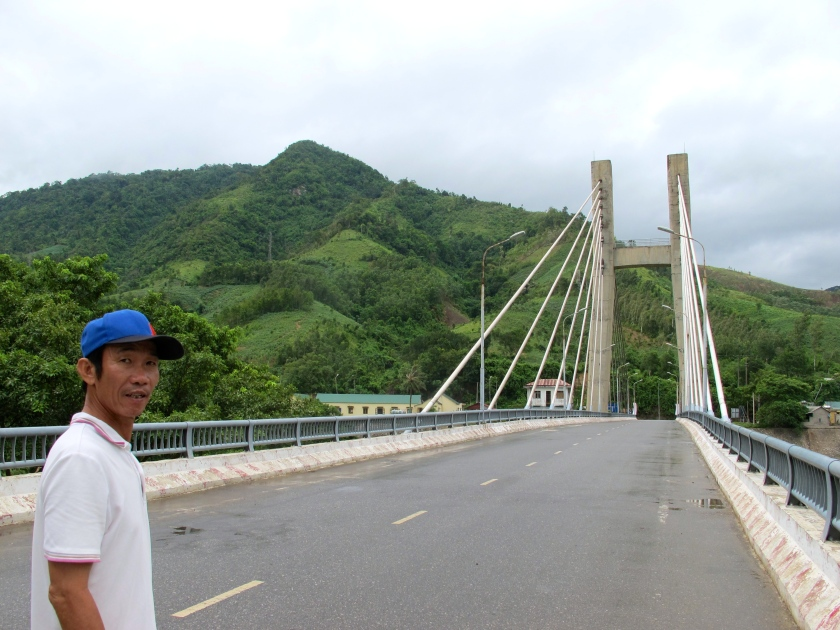 Hoa Tran, my guide, shows me the Dakrong Bridge that   crosses the Han River. (Photo by Nissa Rhee, June 2014)