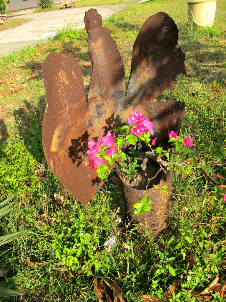 A discarded UXO is used as a flower pot in the garden outside of the Project Renew office. (Photo by Nissa Rhee, June 2014).