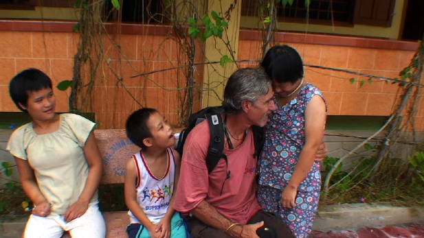 Joe Sciacca embraces two children he helps in Vietnam. (Photo from Ordinary Joe movie site)