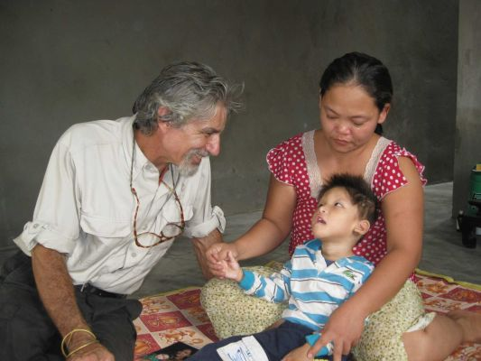 Joe visits a boy in Hue in 2009 who is struggling with the effects of Agent Orange. (Photo from Newsday)
