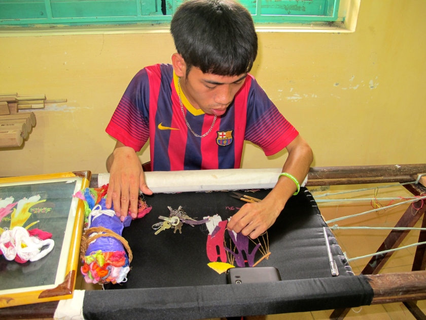A student practices embroidery in a classroom at Friendship Village.
