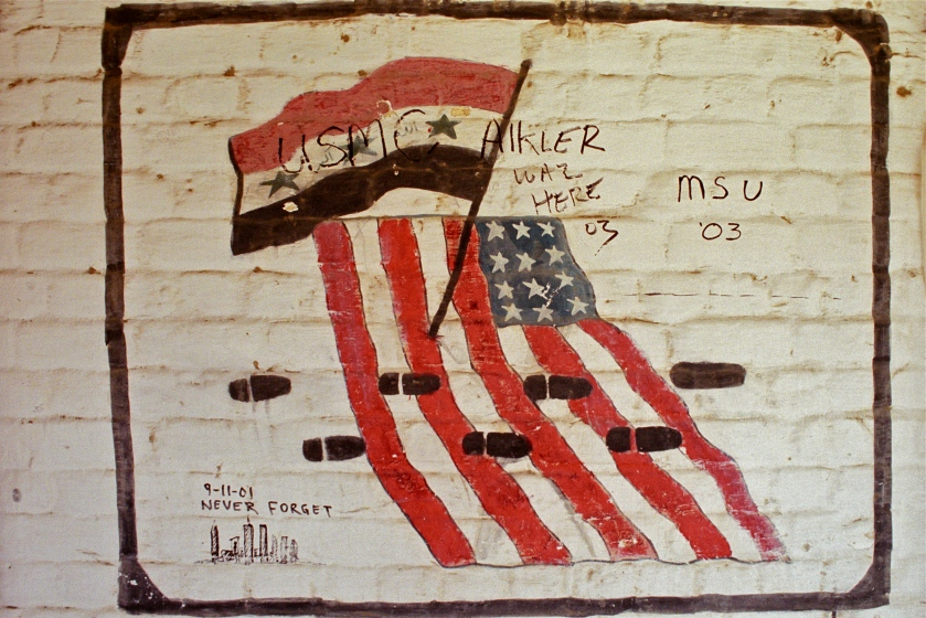 Graffiti from a Marine unit on an abandoned Iraqi military barracks shows the Iraqi and American flags in 2003. Photo taken by Benjamin Busch.